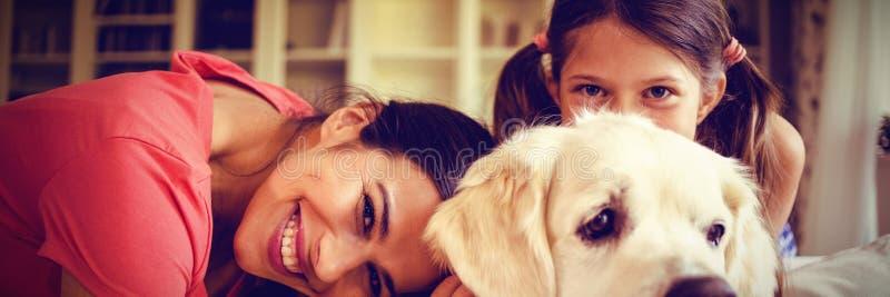 Madre e hija con el perro que se sienta en sala de estar imagenes de archivo