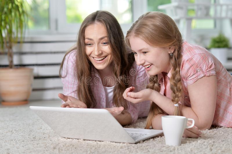 Madre e hija con la computadora portátil fotos de archivo