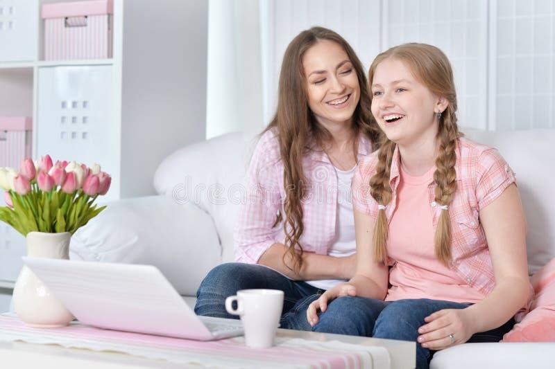 Madre e hija con la computadora portátil imagen de archivo libre de regalías