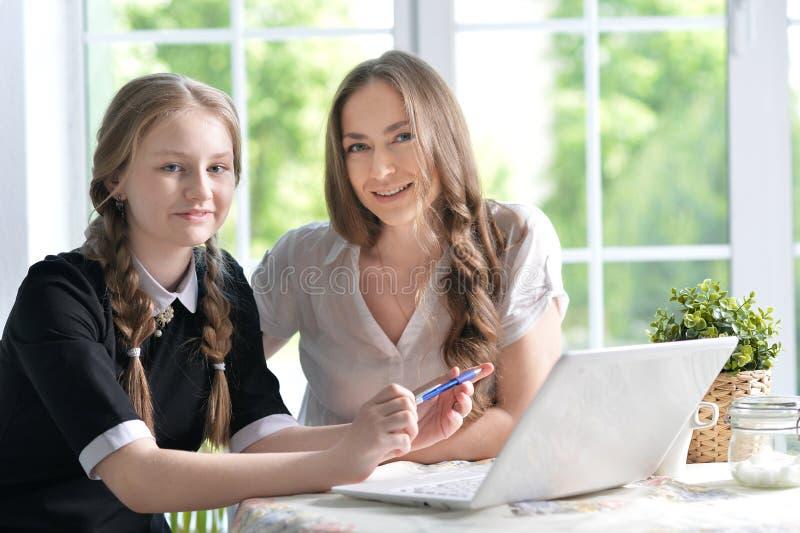Madre e hija con la computadora portátil foto de archivo