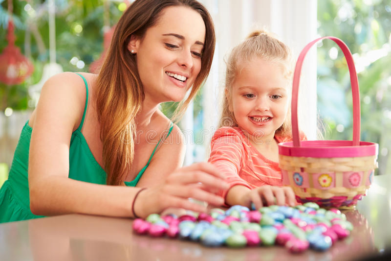 Madre e hija con los huevos y la cesta de Pascua del chocolate imagen de archivo