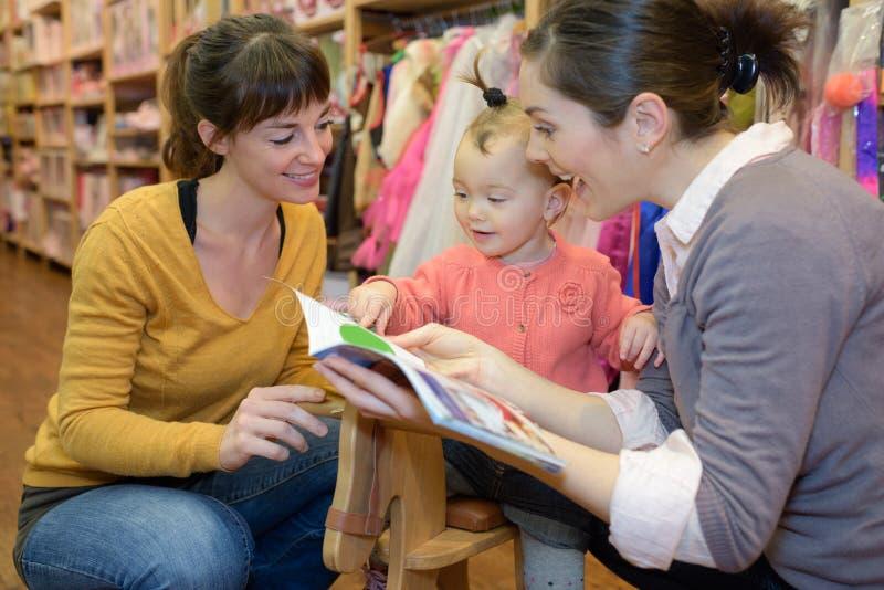 Madre e hija con un vendedor atractivo en una tienda de juguetes imagenes de archivo