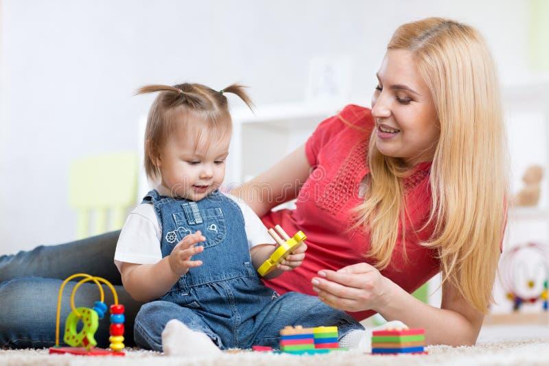 Madre e hija dentro que juegan y que sonríen imagen de archivo