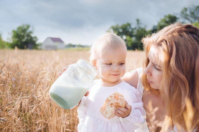 Madre e hija en campo de trigo Familia feliz al aire libre niño sano con la madre en comida campestre con pan y leche en cerea de imagen de archivo