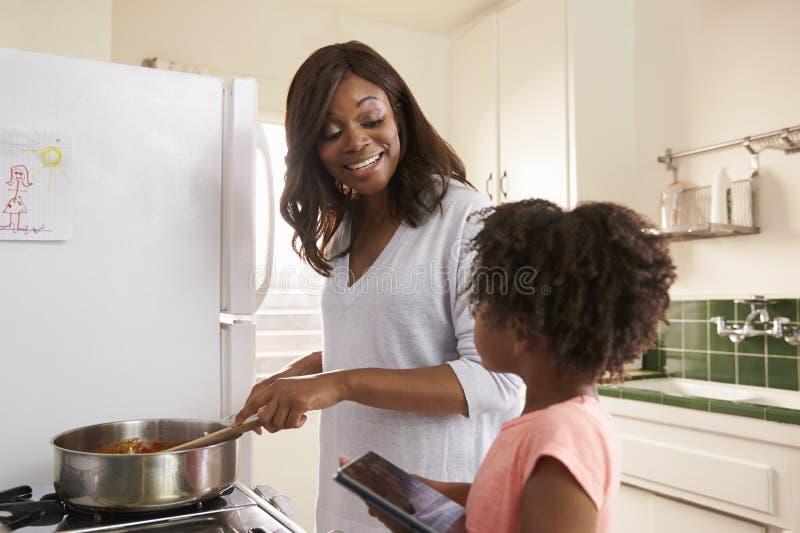 Madre e hija en casa que preparan la comida en cocina imagen de archivo