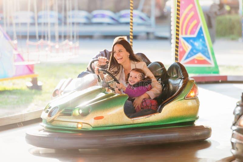 Madre e hija en coche de parachoques en la feria de diversión imágenes de archivo libres de regalías