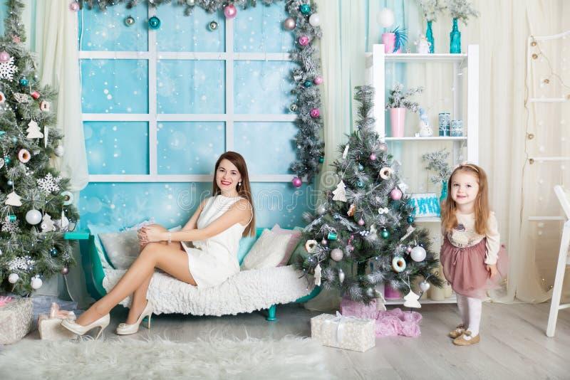 Madre e hija en decoraciones de una Navidad foto de archivo