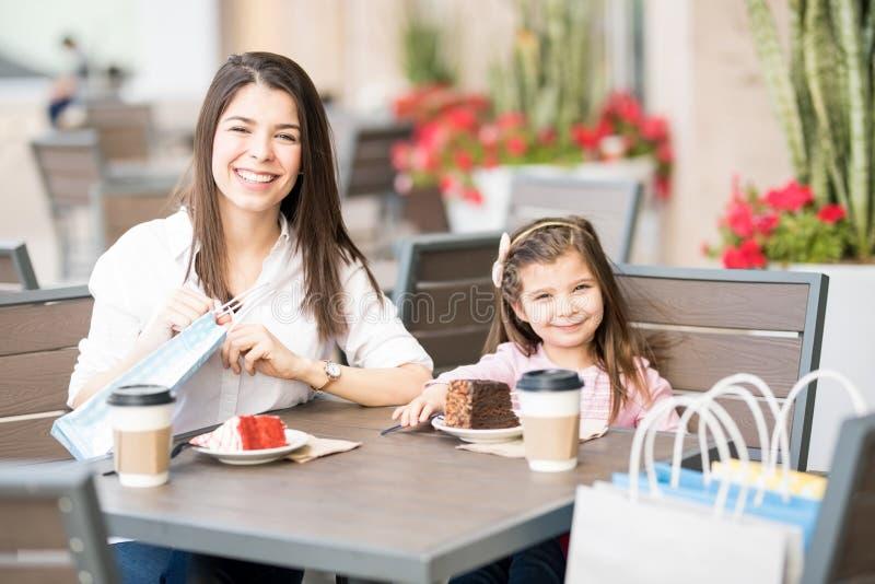 Madre e hija en el café después de hacer compras fotografía de archivo