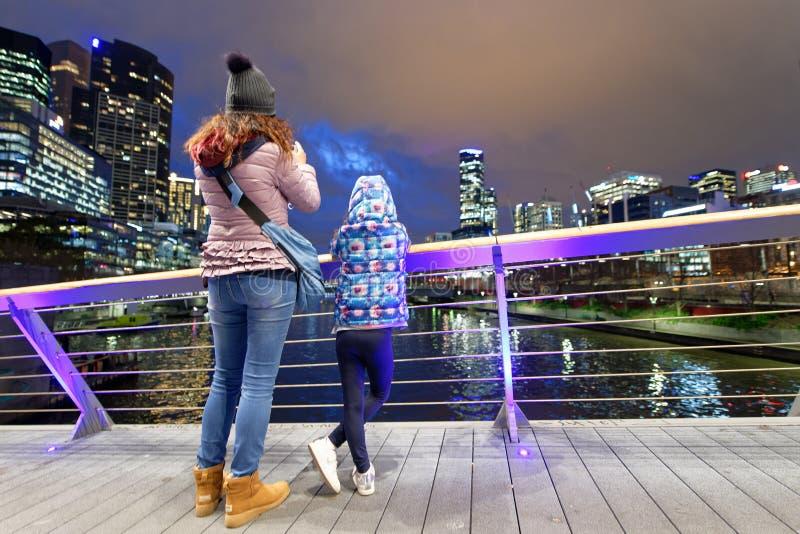 Madre e hija en el horizonte de fotografía de la ciudad de la noche del bea imagen de archivo
