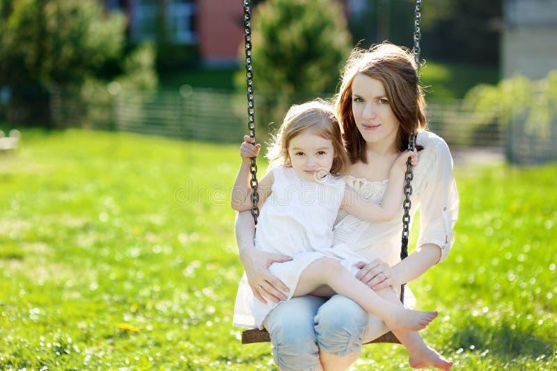 Madre e hija en el oscilación del jardín foto de archivo
