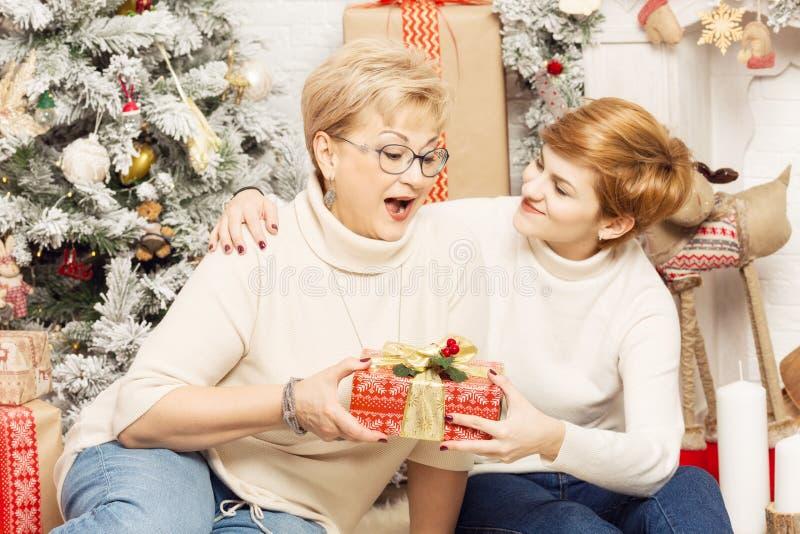 Madre e hija en el ` s del Año Nuevo interior, dando los regalos fotos de archivo libres de regalías