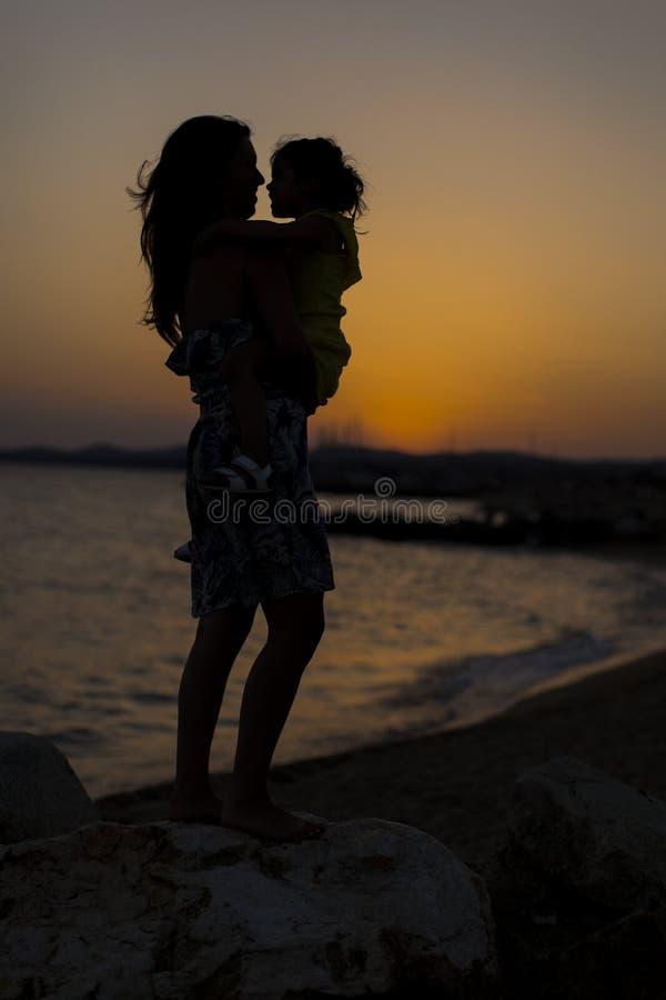 Madre e hija en la playa en la puesta del sol foto de archivo