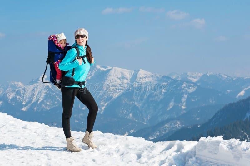Madre e hija en montañas del invierno imagenes de archivo