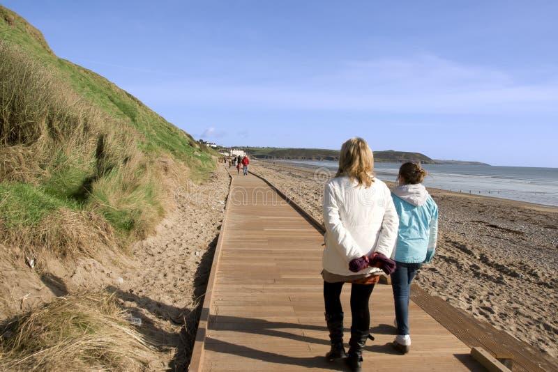 Madre e hija en paseo mar?timo de la playa imagenes de archivo