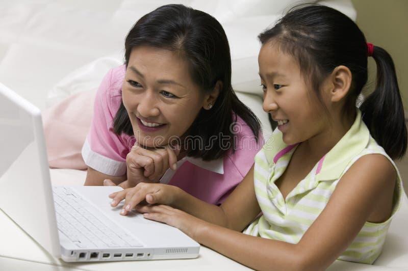 Madre e hija en sala de estar usando el ordenador portátil junto foto de archivo