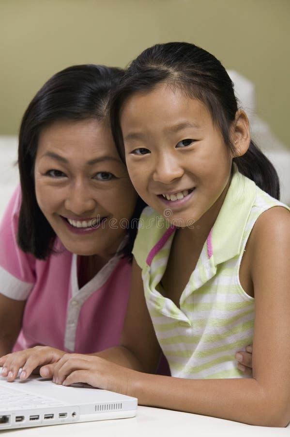 Madre e hija en sala de estar usando el retrato del ordenador portátil junto fotografía de archivo libre de regalías