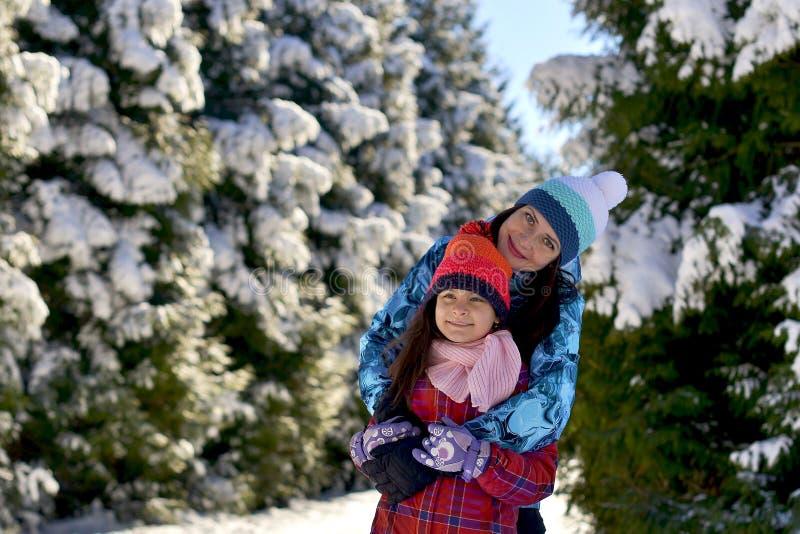 Madre e hija en un paseo en el bosque en un invierno nevoso fotografía de archivo