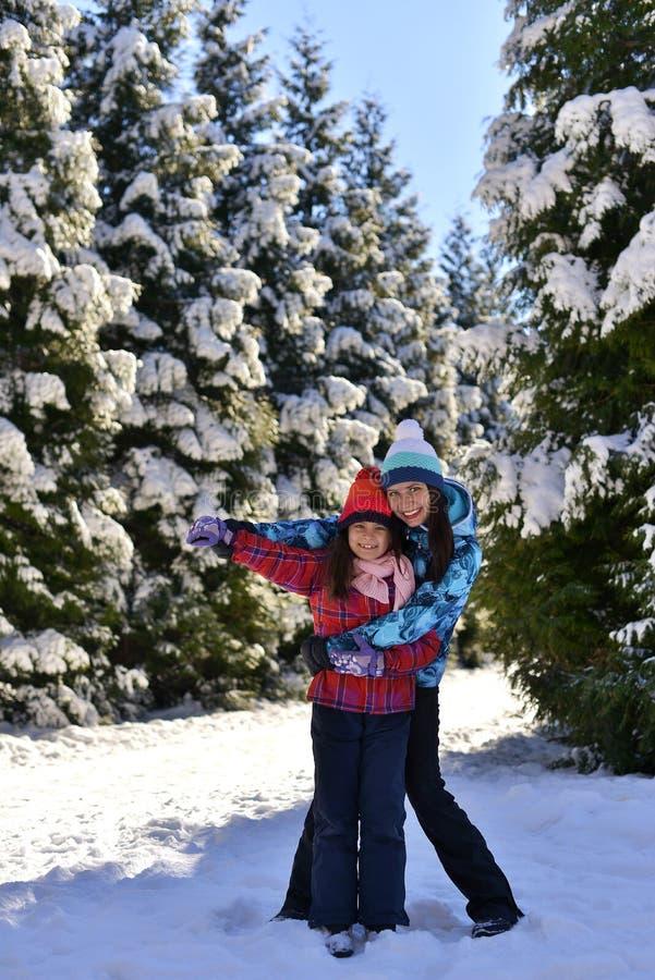 Madre e hija en un paseo en el bosque en un invierno nevoso imagen de archivo libre de regalías