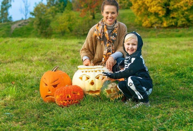 Madre e hija entre las calabazas Jack Oâ de Halloween €™Lantern foto de archivo libre de regalías