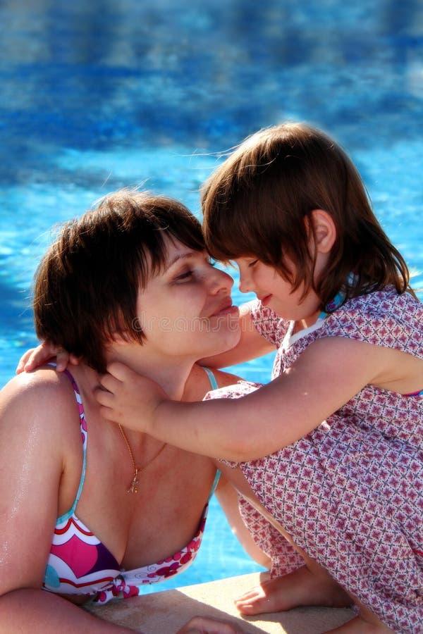 Madre e hija felices al lado de una piscina imagenes de archivo