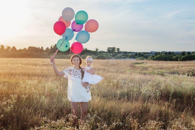 Madre e hija felices con los globos en la puesta del sol imágenes de archivo libres de regalías