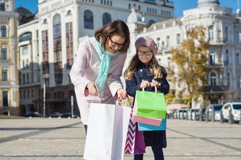 Madre e hija felices con los panieres, fondo urbano del estilo Venta, consumerismo y concepto de la gente imagen de archivo