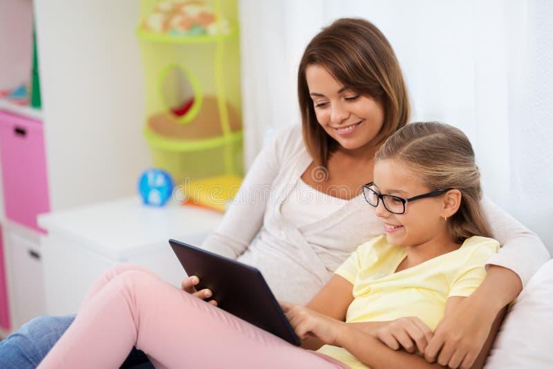 Madre e hija felices con PC de la tableta en casa fotografía de archivo