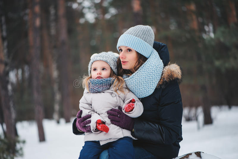 Madre e hija felices en el paseo en invierno nevoso fotos de archivo
