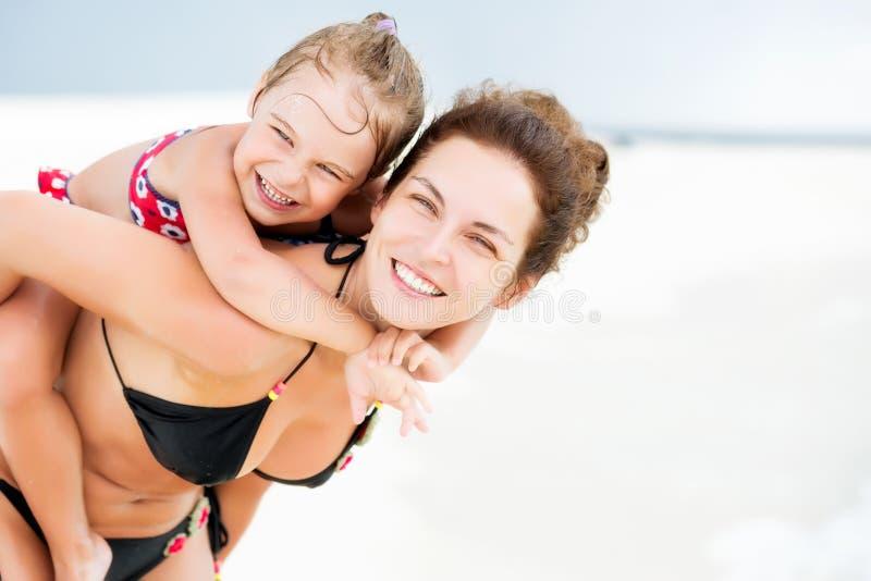 Madre e hija felices en la playa del océano en Maldivas en las vacaciones de verano imágenes de archivo libres de regalías