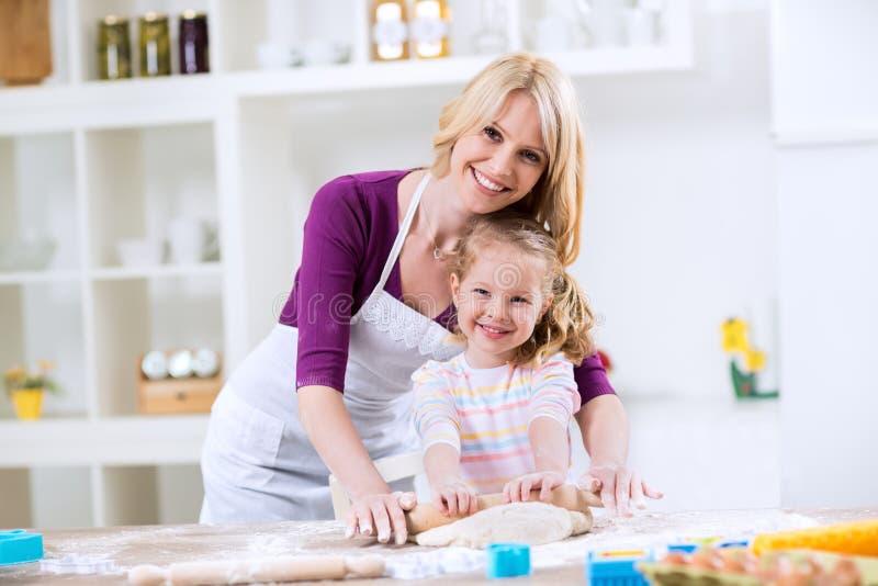 Madre e hija felices sonrientes en la cocina fotos de archivo libres de regalías