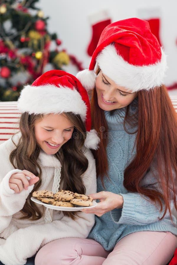 Madre e hija festivas en el sofá con las galletas foto de archivo libre de regalías