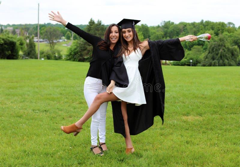 Madre e hija hermosas en el casquillo, el vestido y Tass negros, adolescente atractivo Cara magnífica única, sonrisa agradable, m fotografía de archivo