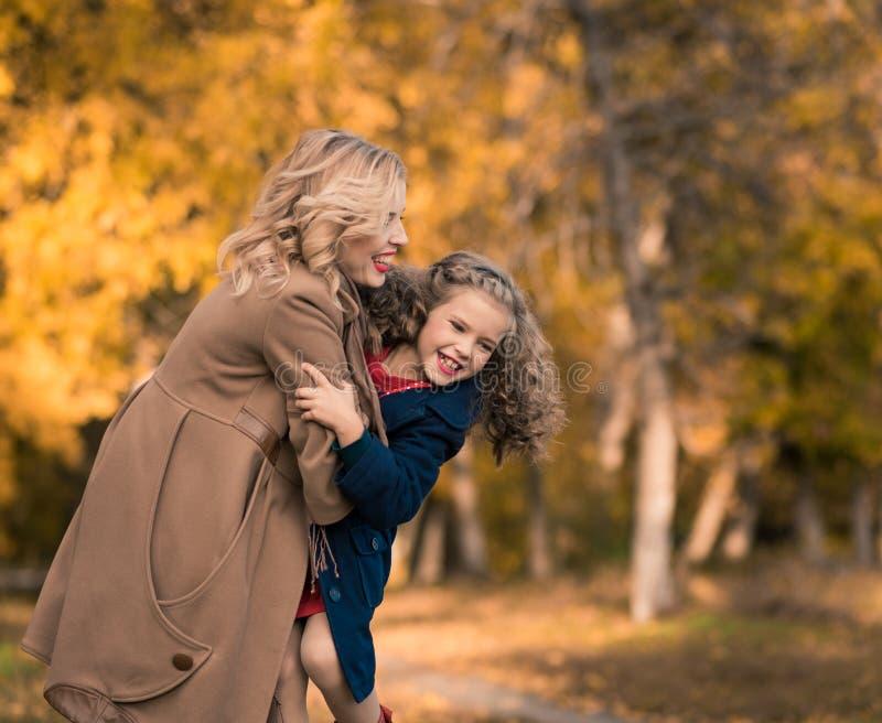 Madre e hija hermosas en otoño colorido al aire libre fotografía de archivo