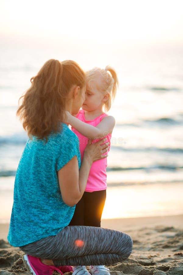 Madre e hija jovenes aptas en la playa que da besos del esquimal fotos de archivo libres de regalías