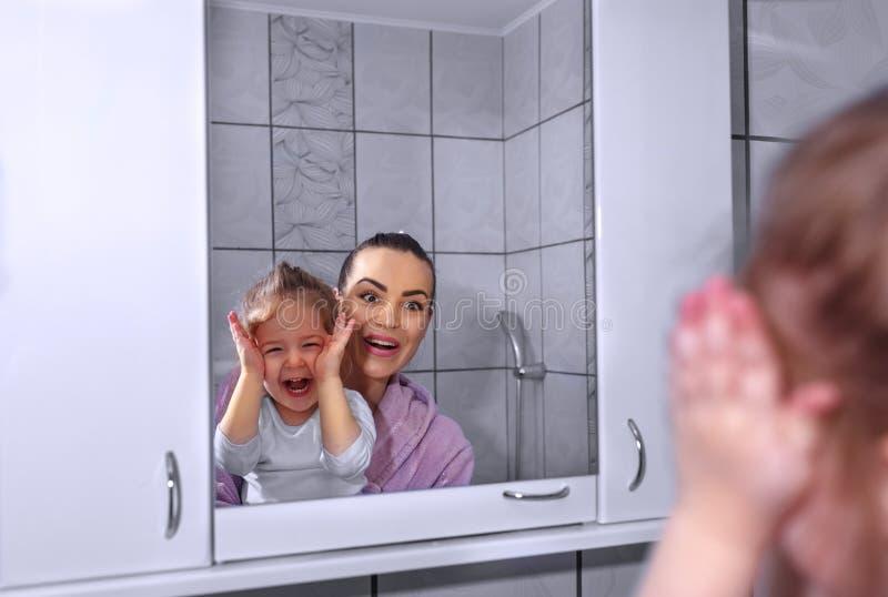 Madre e hija jovenes en un abrazo sonriente feliz del cuarto de baño cada o imagen de archivo libre de regalías