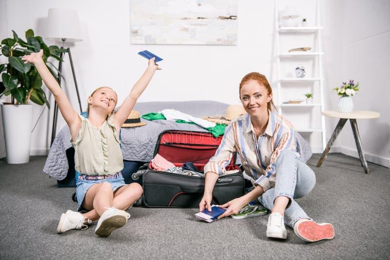 madre e hija jovenes felices con equipaje y pasaportes imagen de archivo