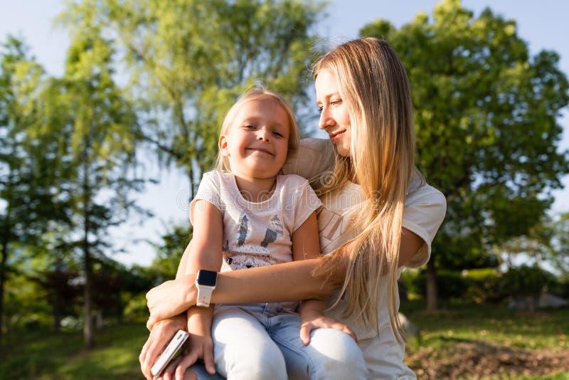 Madre e hija jovenes hermosas con el abarcamiento del pelo rubio al aire libre Muchachas elegantes que hacen caminar en el parque imagenes de archivo