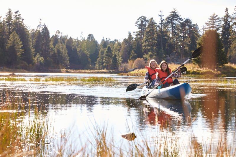 Madre e hija kayaking en el lago, vista delantera fotografía de archivo libre de regalías