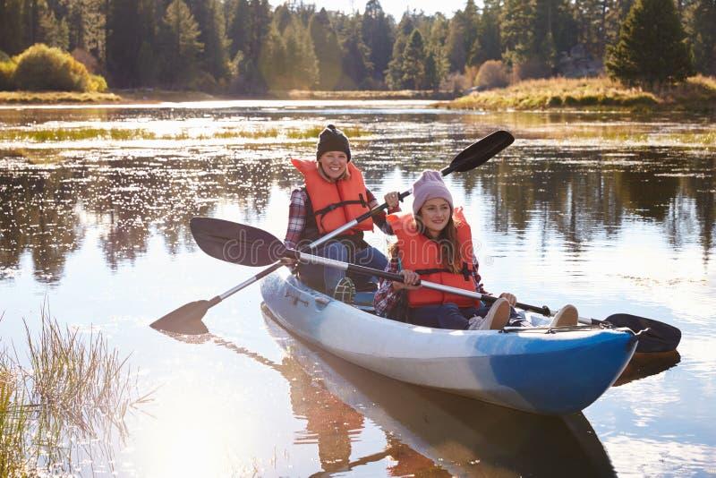 Madre e hija kayaking en el lago, vista delantera, primer fotografía de archivo