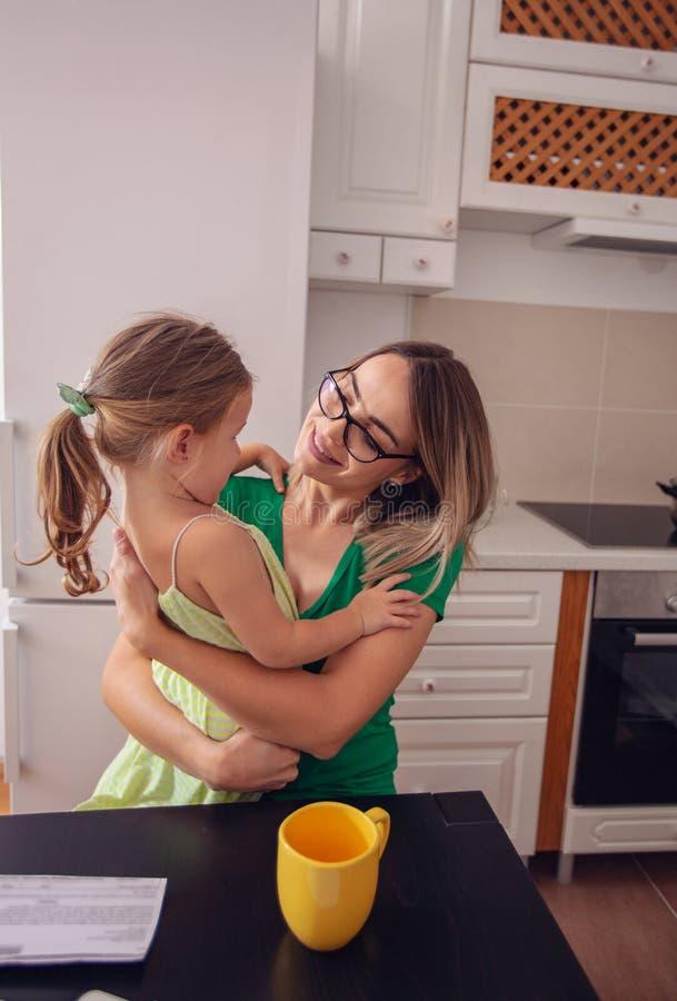 Madre e hija linda que gozan en casa, feliz, sonriendo foto de archivo libre de regalías