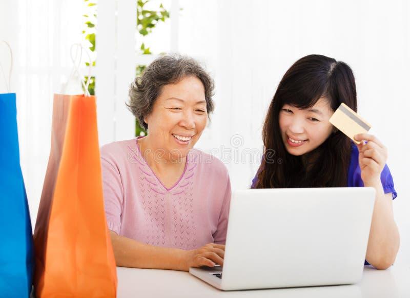 Madre e hija mayores felices con el ordenador portátil y la tarjeta de crédito imagen de archivo libre de regalías