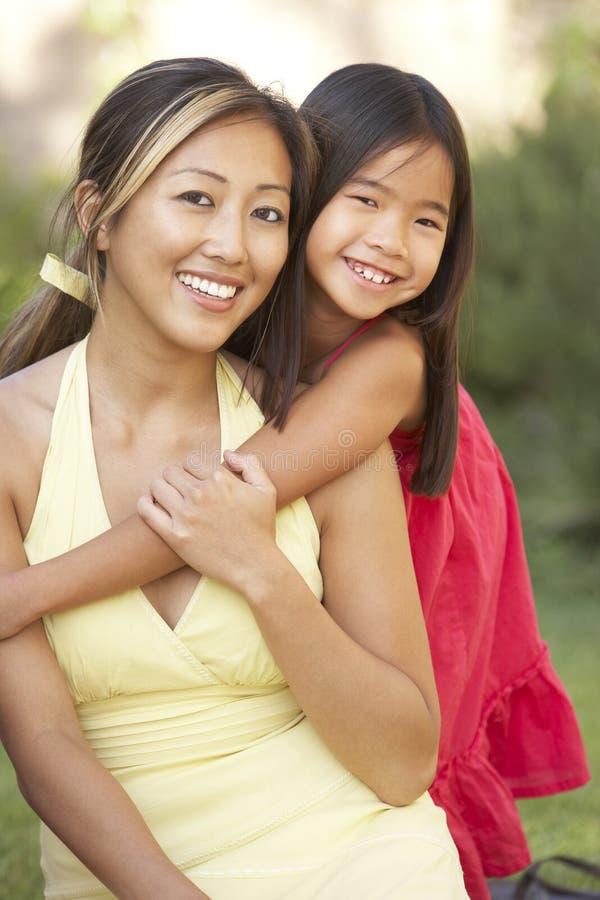 Madre e hija que abrazan en jardín foto de archivo