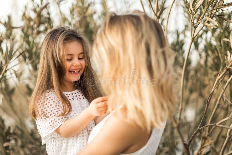Madre e hija que abrazan en naturaleza en el verano fotos de archivo