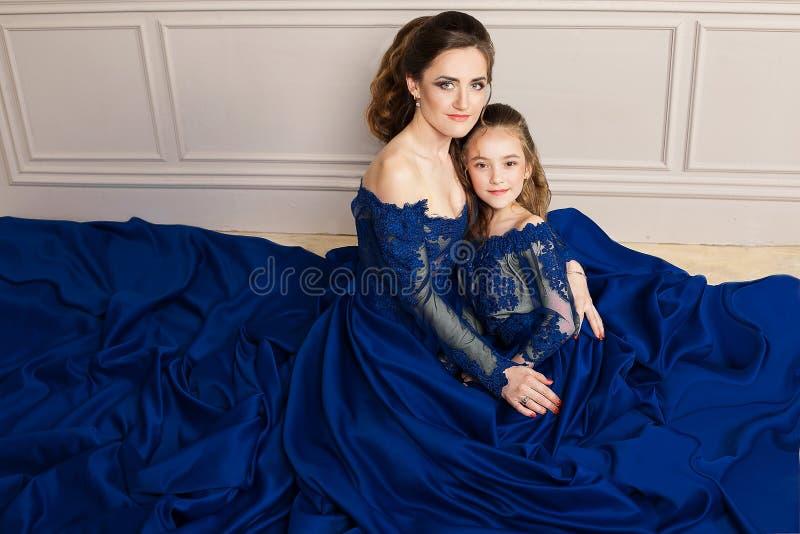 Madre e hija que abrazan y que miran la cámara Familia cariñosa feliz Madre e hija en dres azules de lujo largos hermosos foto de archivo