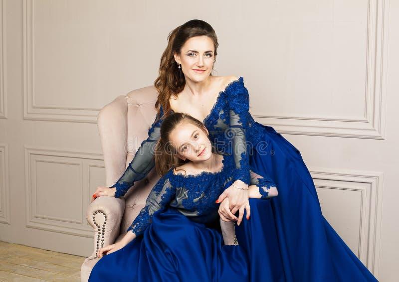 Madre e hija que abrazan y que miran la cámara Familia cariñosa feliz Madre e hija en dres azules de lujo largos hermosos fotos de archivo libres de regalías