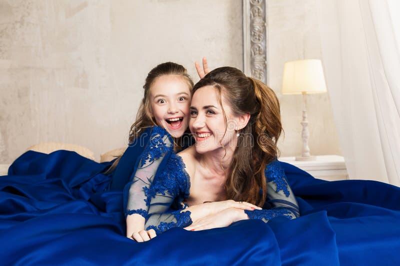 Madre e hija que abrazan y que miran la cámara Familia cariñosa feliz Madre e hija en dres azules de lujo largos hermosos imagenes de archivo