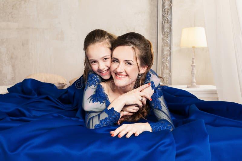 Madre e hija que abrazan y que miran la cámara Familia cariñosa feliz Madre e hija en dres azules de lujo largos hermosos fotografía de archivo
