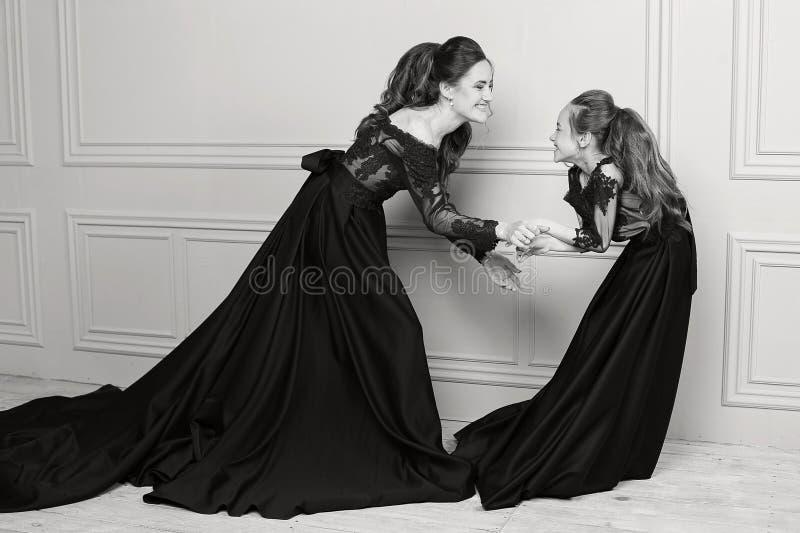 Madre e hija que abrazan y que miran la cámara Familia cariñosa feliz Madre e hija en dres azules de lujo largos hermosos fotografía de archivo libre de regalías