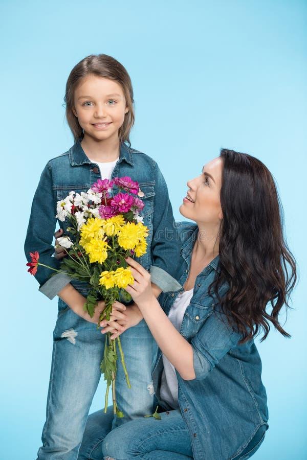 Madre e hija que abrazan y que sostienen las flores en estudio en día de madres azul, feliz imagenes de archivo