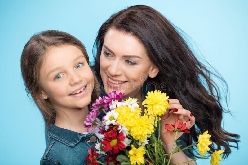 Madre e hija que abrazan y que sostienen las flores en estudio en día de madres azul, feliz fotografía de archivo libre de regalías